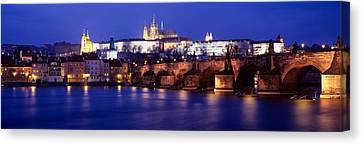 Bridge Across A River Lit Up At Night Canvas Print by Panoramic Images