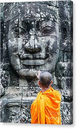 Cambodia - Angkor Wat - Monk Touching Giant Buddha Statue Canvas Print by Matteo Colombo