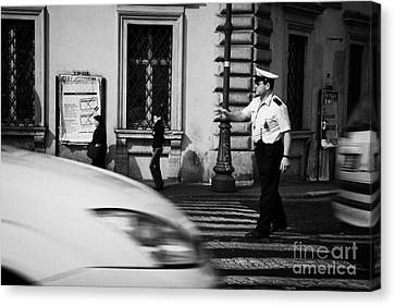 car drives across crossing as Roman Municipal policeman directs traffic at a pedestrian crossing in the Via Teatro Marcello Rome Lazio Italy Canvas Print by Joe Fox
