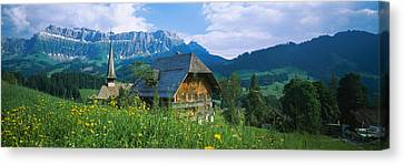 Chalet And A Church On A Landscape Canvas Print by Panoramic Images