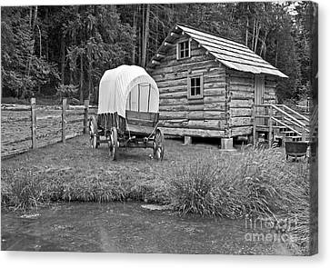 Covered Wagon Near Log Cabin Black And White Canvas Print by Valerie Garner