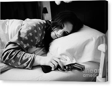 Early Twenties Woman With Hand On Handgun Under Pillow At Night In Bed In A Bedroom Canvas Print by Joe Fox