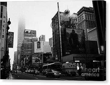 empire state building shrouded in mist from west 34th Street and 7th Avenue new york city usa Canvas Print by Joe Fox
