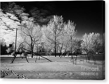 empty childrens playground with hoar frost covered trees on street in small rural village of Forget  Canvas Print by Joe Fox