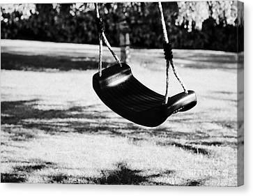 Empty Plastic Swing Swinging In A Garden In The Evening Canvas Print by Joe Fox