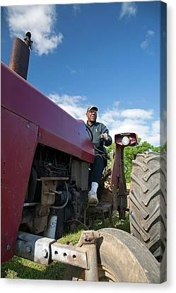 Farmer On A Tractor Canvas Print by Jim West