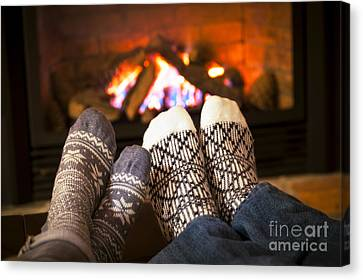Feet Warming By Fireplace Canvas Print by Elena Elisseeva