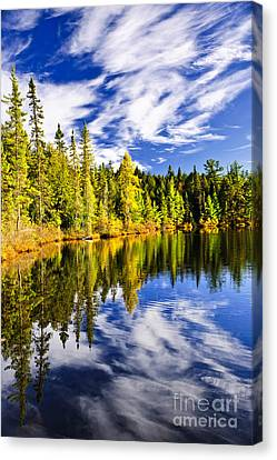Forest And Sky Reflecting In Lake Canvas Print by Elena Elisseeva