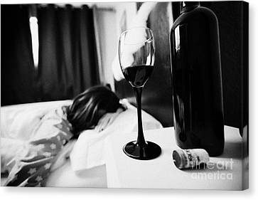 Half Full Glass Of Wine On Bedside Table Of Early Twenties Woman In Bed In A Bedroom Canvas Print by Joe Fox