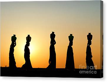 Indian Women Carrying Water Pots At Sunset Canvas Print by Tim Gainey