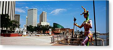 Jester Statue With Buildings Canvas Print by Panoramic Images