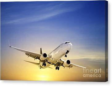 Jet Aeroplane Landing At Sunset Blue Yellow  Canvas Print by Colin and Linda McKie