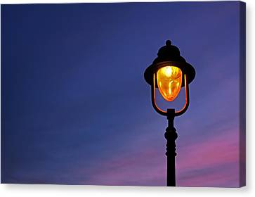 Lamppost Illuminated At Twilight Canvas Print by Mikel Martinez de Osaba