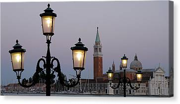 Lampposts Lit Up At Dusk With Building Canvas Print by Panoramic Images