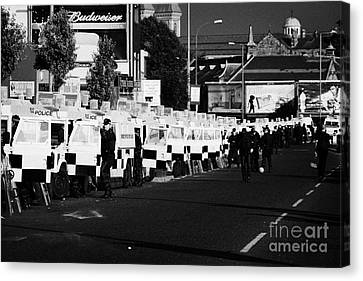 Line Of Psni Land Rovers And Officers On Crumlin Road At Ardoyne Shops Belfast 12th July Canvas Print by Joe Fox