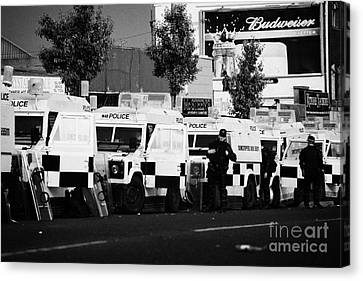 Line Of Psni Landrovers And Officers On Crumlin Road At Ardoyne Shops Belfast 12th July Canvas Print by Joe Fox
