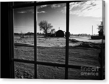 looking out through door window to snow covered scene in small rural village of Forget Saskatchewan  Canvas Print by Joe Fox