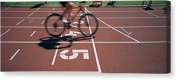 Low Section View Of A Man Cycling Canvas Print by Panoramic Images