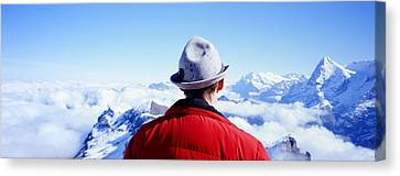 Man Contemplating Swiss Alps Canvas Print by Panoramic Images