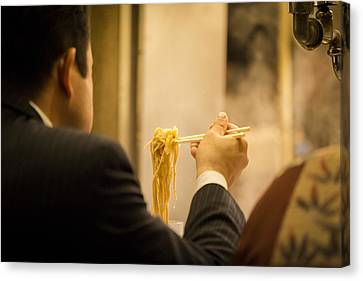 Man Eating Noodles In A Restaurant Canvas Print by Ruben Vicente