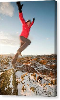 Man Leaping Off Rock Canvas Print by Ashley Cooper