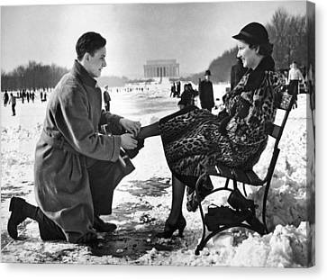 Man Lends A Helping Hand To Put On Skates Canvas Print by Underwood Archives
