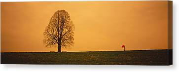 Man Standing With An Umbrella Canvas Print by Panoramic Images