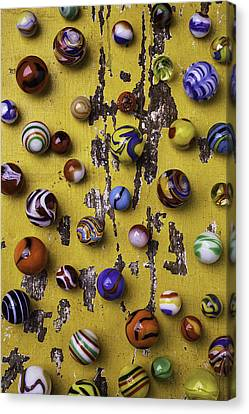 Marbles On Yellow Wooden Table Canvas Print by Garry Gay