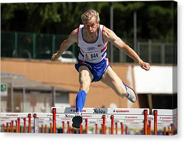 Masters British Athlete Clearing Hurdle Canvas Print by Alex Rotas