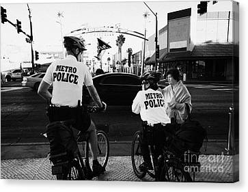 metro police bicycle cops help a tourist with directions in downtown Las Vegas Nevada USA Canvas Print by Joe Fox