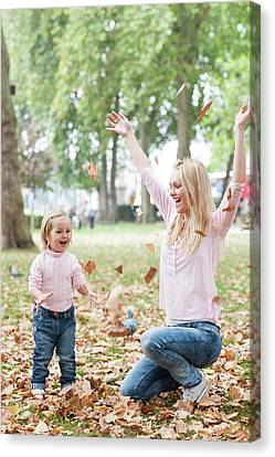 Mother And Daughter Playing With Leaves Canvas Print by Ian Hooton