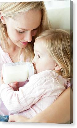 Mother Feeding Daughter With Bottle Canvas Print by Ian Hooton