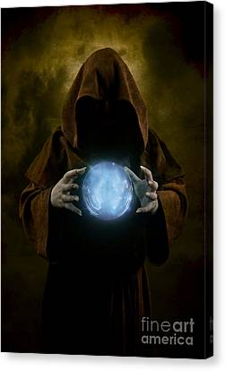Mystery Man Wearing Cloak With Hood And Blue Glowing Crystal Ball Between His Hands Canvas Print by Jaroslaw Blaminsky
