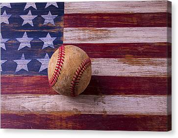 Old Baseball On American Flag Canvas Print by Garry Gay