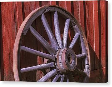 Old Wagon Wheel Leaning Against Barn Canvas Print by Garry Gay