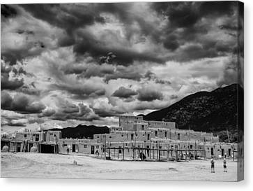 Ominous Clouds Over Taos Pueblo Canvas Print by Silvio Ligutti