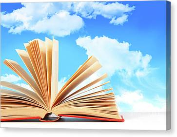 Open Book Against A Blue Sky Canvas Print by Sandra Cunningham