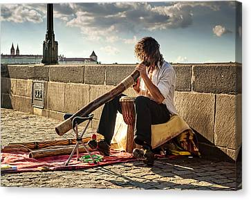 Playing Didgeridoo On The Charles Bridge. Prague Canvas Print by Jenny Rainbow