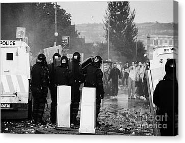 Police Officers In Riot Gear Face Rioters On Crumlin Road At Ardoyne Canvas Print by Joe Fox