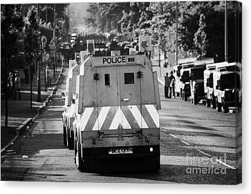Psni Land Rovers Head Up The Crumlin Road Towards Loyalists At Ardoyne Shops Belfast 12th July Canvas Print by Joe Fox