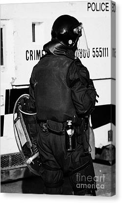 Psni Officer With Riot Gear On Crumlin Road At Ardoyne Shops Belfast 12th July Canvas Print by Joe Fox