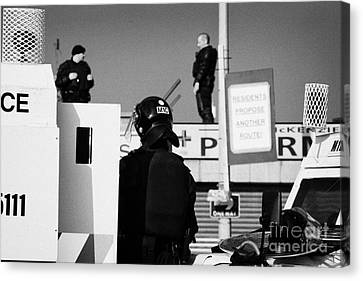 Psni Officers In Protective Riot Gear At Landrovers And Snipers On Crumlin Road At Ardoyne Shops Bel Canvas Print by Joe Fox