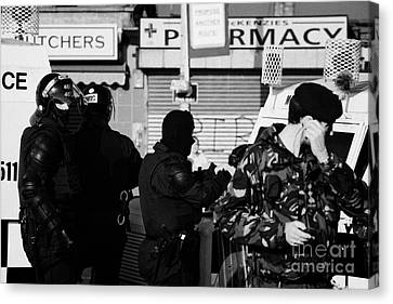 Psni Riot Officers And British Soldier On Crumlin Road At Ardoyne Shops Belfast 12th July Canvas Print by Joe Fox