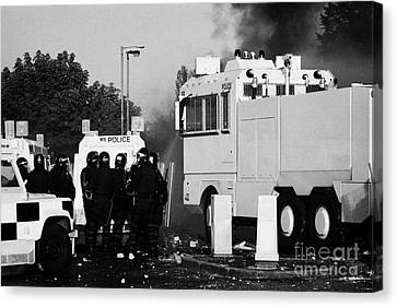 Psni Riot Officers Behind Armoured Land Rover And Water Cannon On Crumlin Road At Ardoyne Shops Belf Canvas Print by Joe Fox