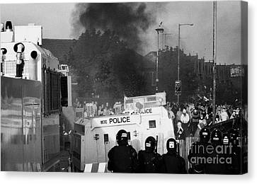 Psni Riot Officers Face Rioters Mob And Burning Vehicle On Crumlin Road At Ardoyne Shops Belfast 12t Canvas Print by Joe Fox