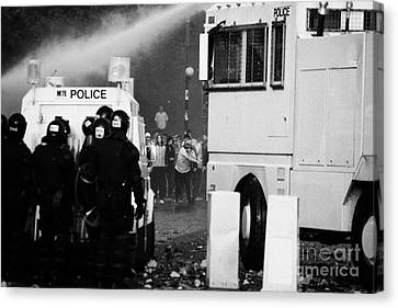 Psni Riot Police Behind Armoured Land Rover And Water Canon Face On Crumlin Road At Ardoyne Canvas Print by Joe Fox