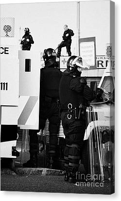 Psni Riot Squad Officers In Protective Gear And Snipers On Crumlin Road At Ardoyne Shops Belfast 12t Canvas Print by Joe Fox