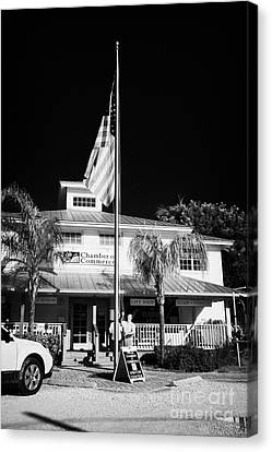 Raising The American Flag On A Flagpole Outside The Chamber Of Commerce Building In Key Largo Florid Canvas Print by Joe Fox