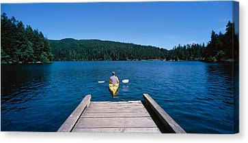 Rear View Of A Man On A Kayak Canvas Print by Panoramic Images