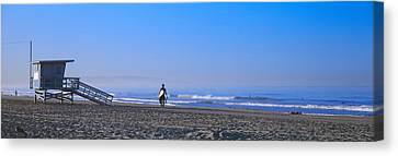 Rear View Of A Surfer On The Beach Canvas Print by Panoramic Images